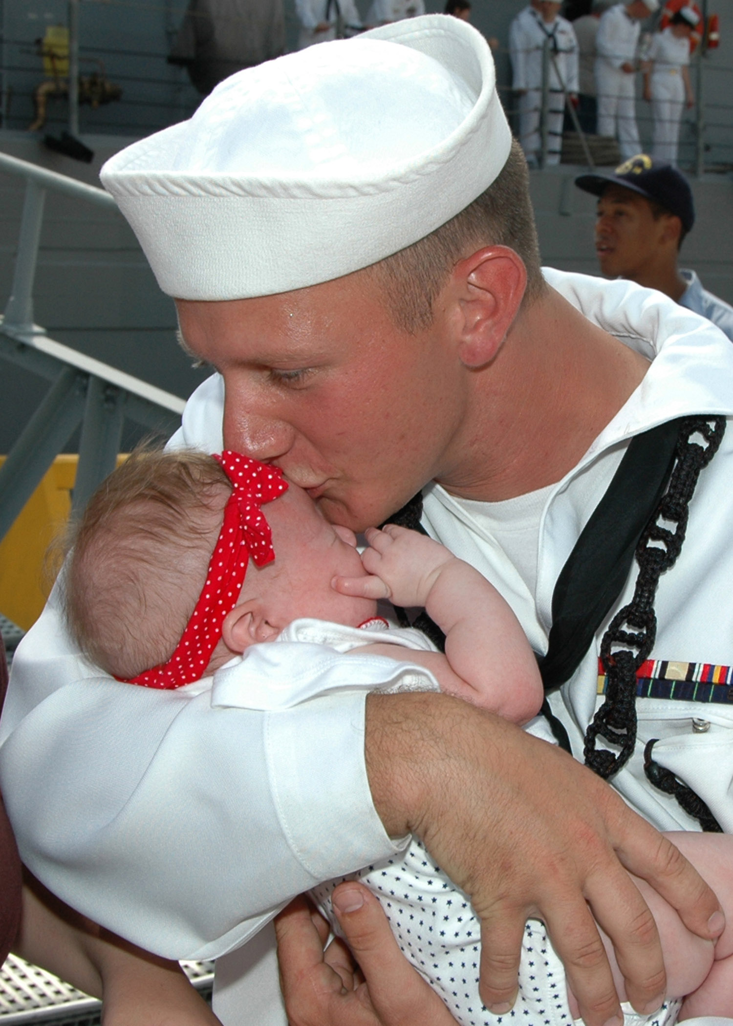 US Navy 070702-N-1522S-075 Boatswain's Mate 3rd Class Christopher Ball kisses his newborn baby, Chloe, for the first time during the homecoming of guided missile frigate USS Underwood (FFG-36)