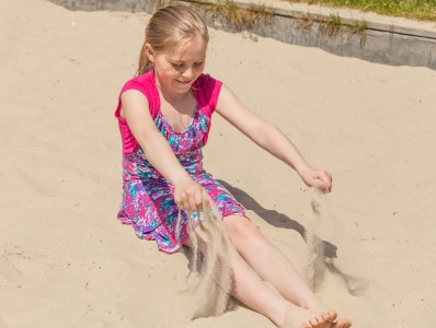 a young Catholic blond girl playing in a sandbox in May 2014, picture 1/3