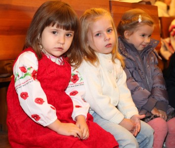 three cute charming beautiful child girls in a Church in a Catholic kindergarten