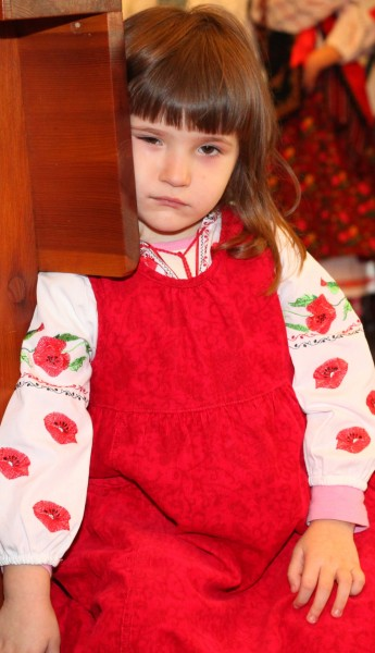 a beautiful amazing cute charming Catholic child girl in a red dress in a Church looks sad, photo 4