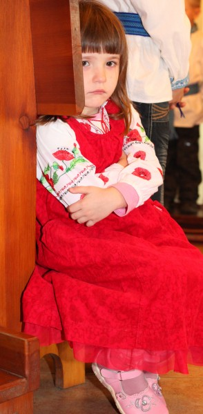 a beautiful amazing cute charming Catholic child girl in a red dress in a Church looks sad, photo 5