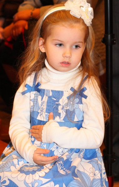 a cute beautiful charming Catholic child girl ina blue dress in a Church, photo 1