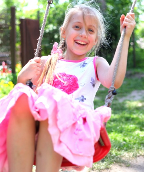 a cute young blond smiling Catholic girl on a swing photographed in May 2013, picture 1