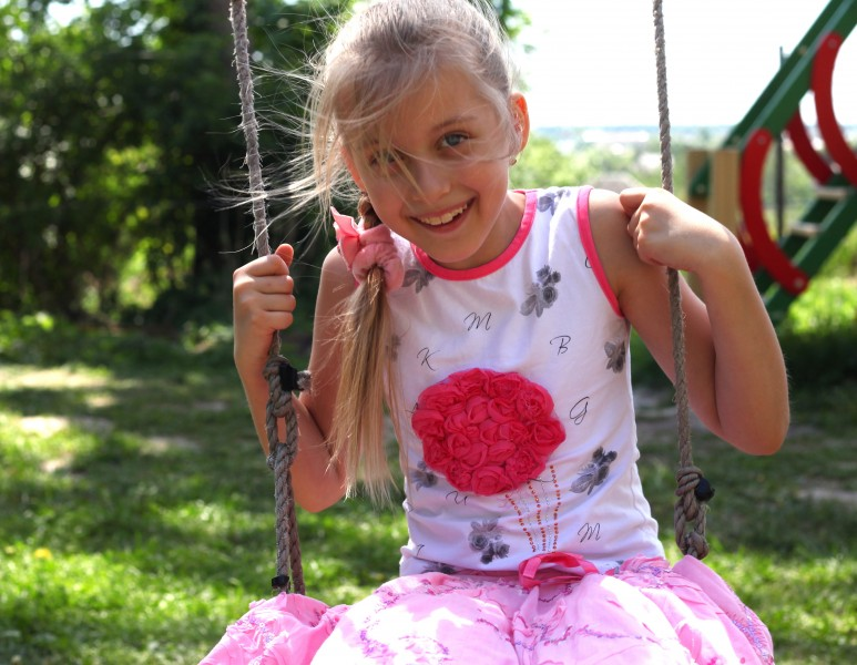 a cute happy young blond Catholic girl on a swing photographed in May 2013, picture 2