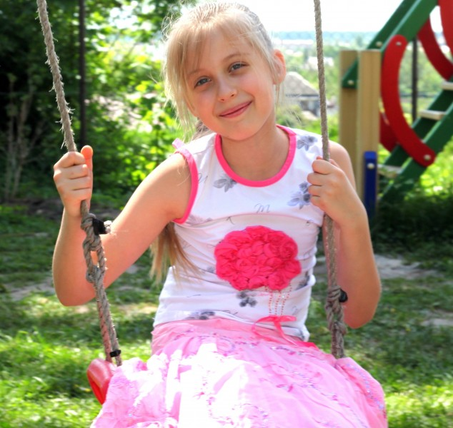 a pretty young blond Catholic girl on a swing photographed in May 2013, picture 3