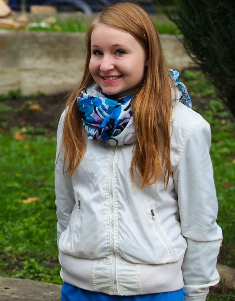 a smiling cute blond girl near a Catholic church photographed in September 2013, picture 1/6