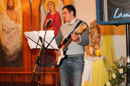 a Catholic man playing an electronic guitar in a Church
