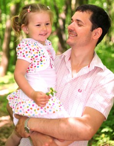 a handsome Catholic father holding his cute daughter in May 2013