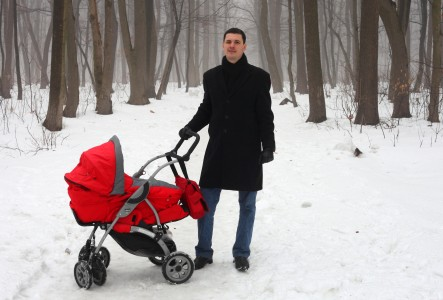 a handsome Catholic man with his baby daughter in a park