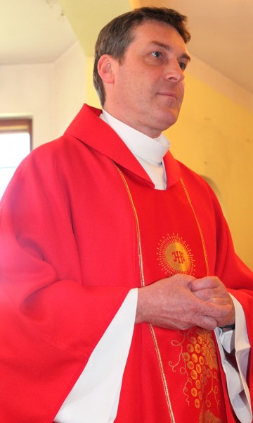 a Catholic priest in red in a church in May 2013, portrait 1
