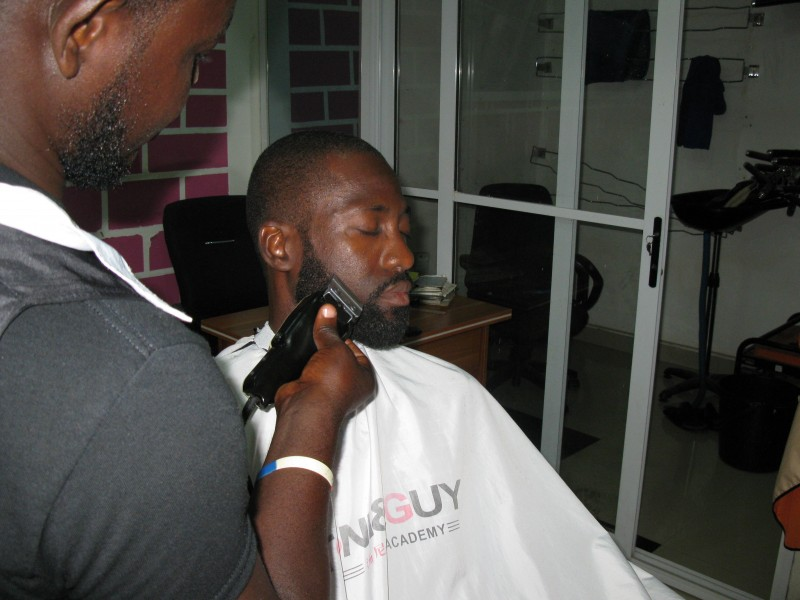 A Ghanaian Barber trimming a beard