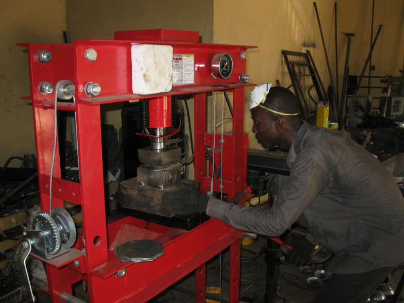 A Ghanaian Metal Fabricator at the hydraulic press