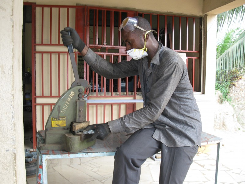 A Ghanaian Metal Fabricator cuts a metal plate