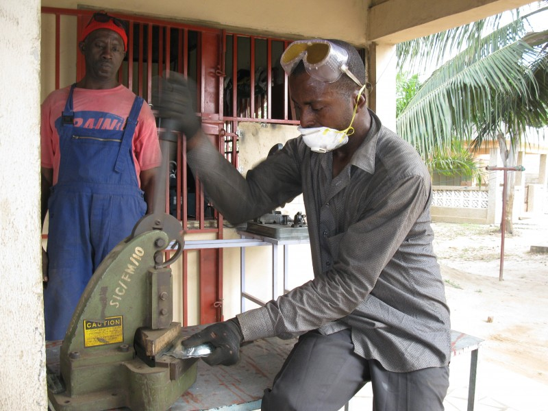 A Ghanaian Metal Fabricator cutting a plate