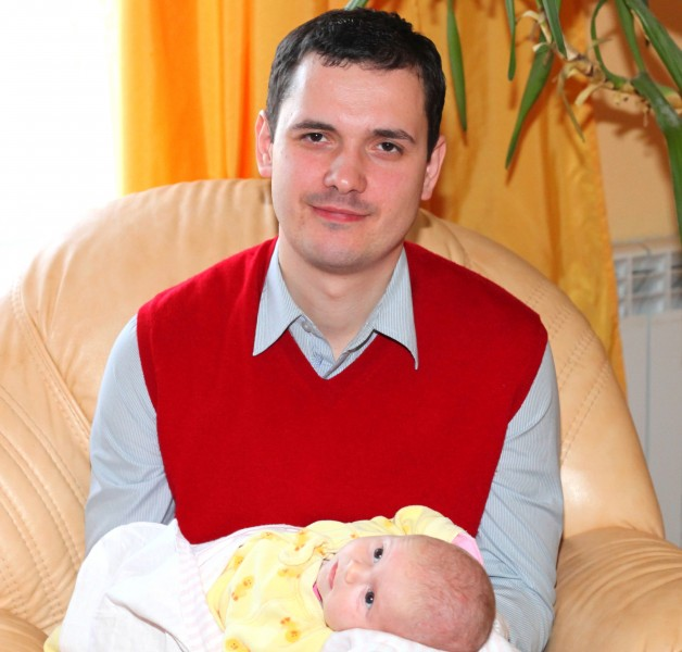 a handsome Catholic man with his baby daughter