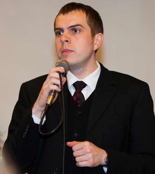 a young man with a microphone photographed in a Catholic chapel in November 2013