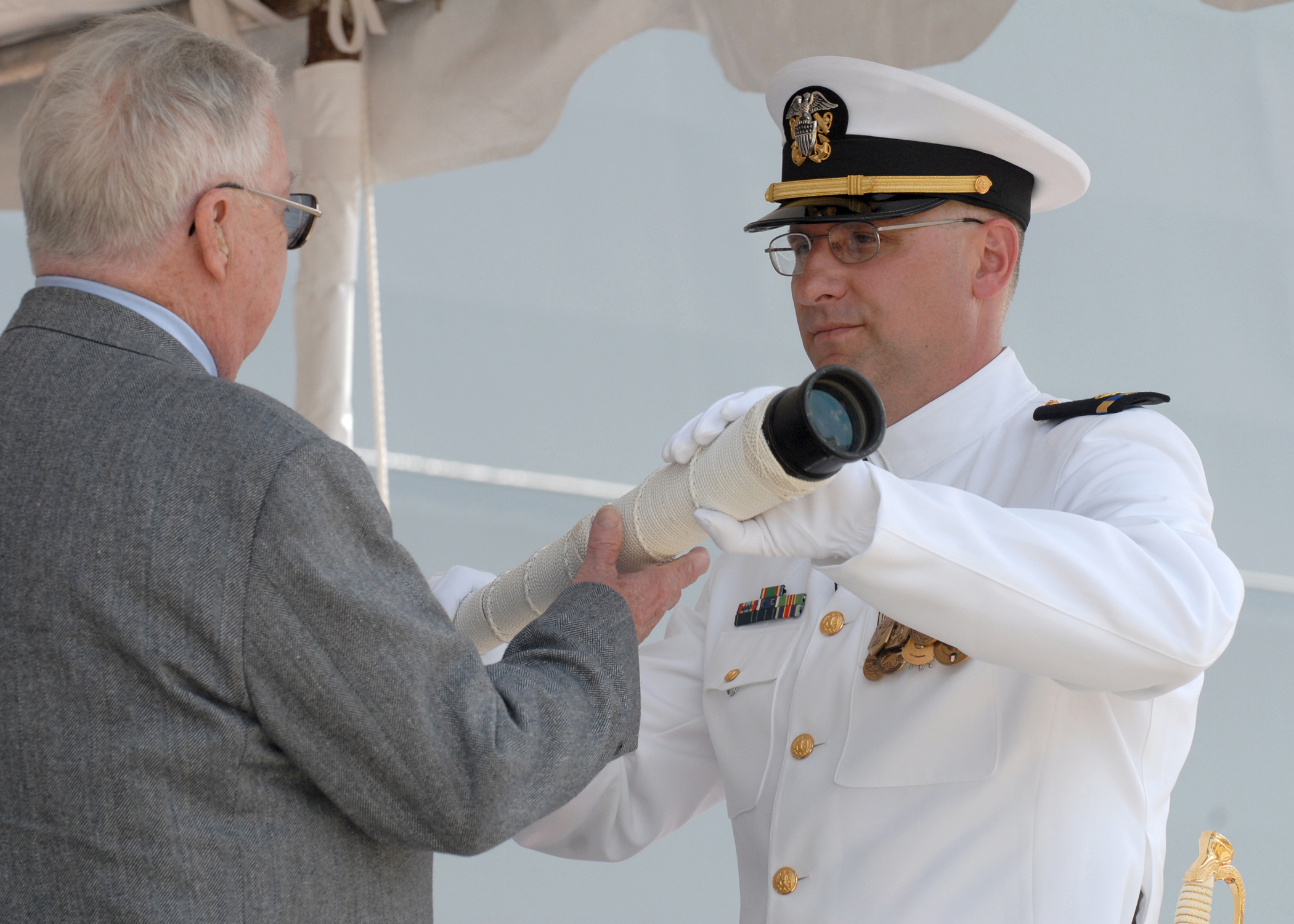 US Navy 070310-N-9909C-002 Retired Senior Chief Fire Control Technician Hank Wristen, passes the ship's long glass to Chief Warrant Officer Robert McLaughlin