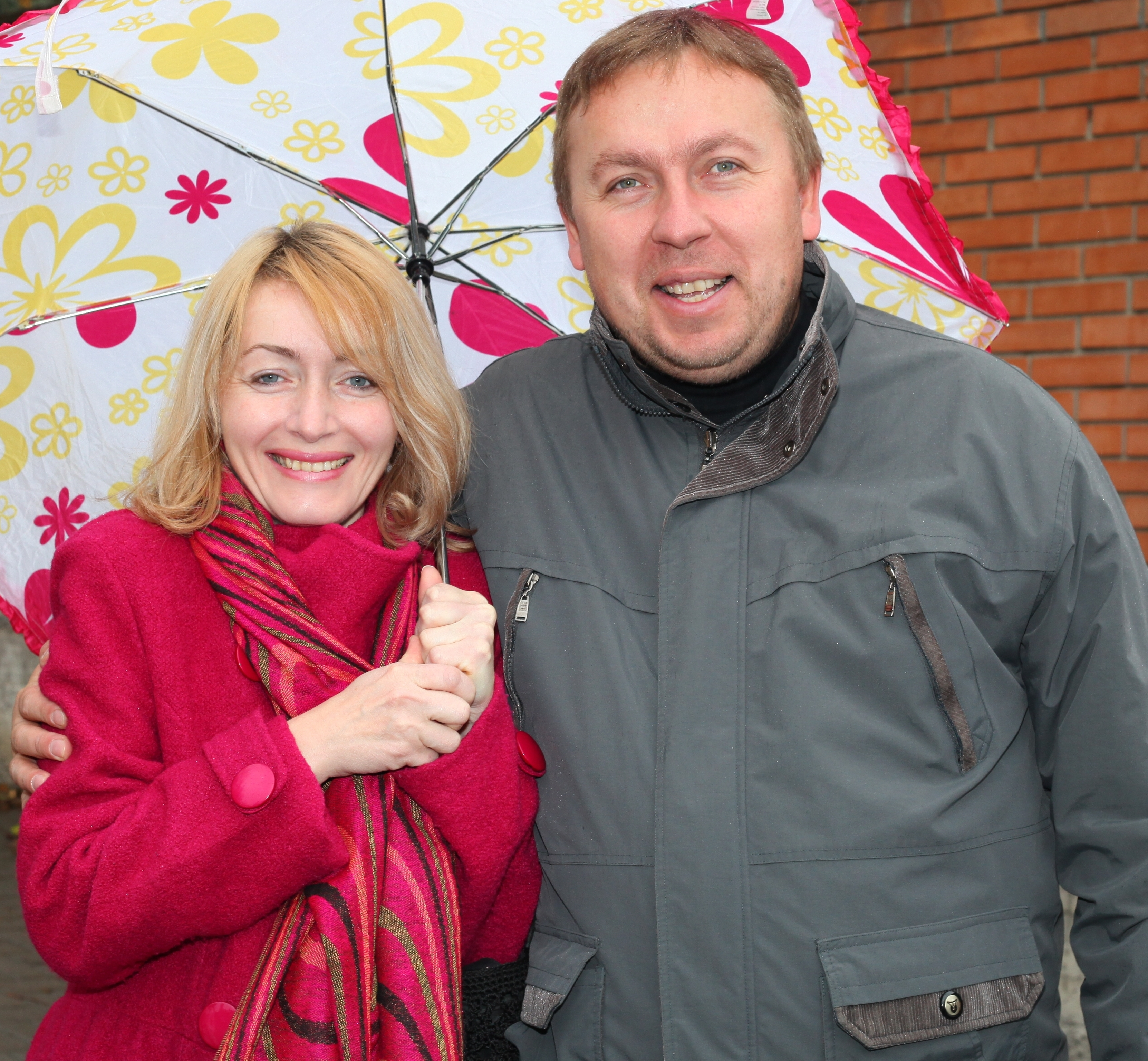 a charming beautiful Catholic woman with an umbrella and a handsome Catholic man