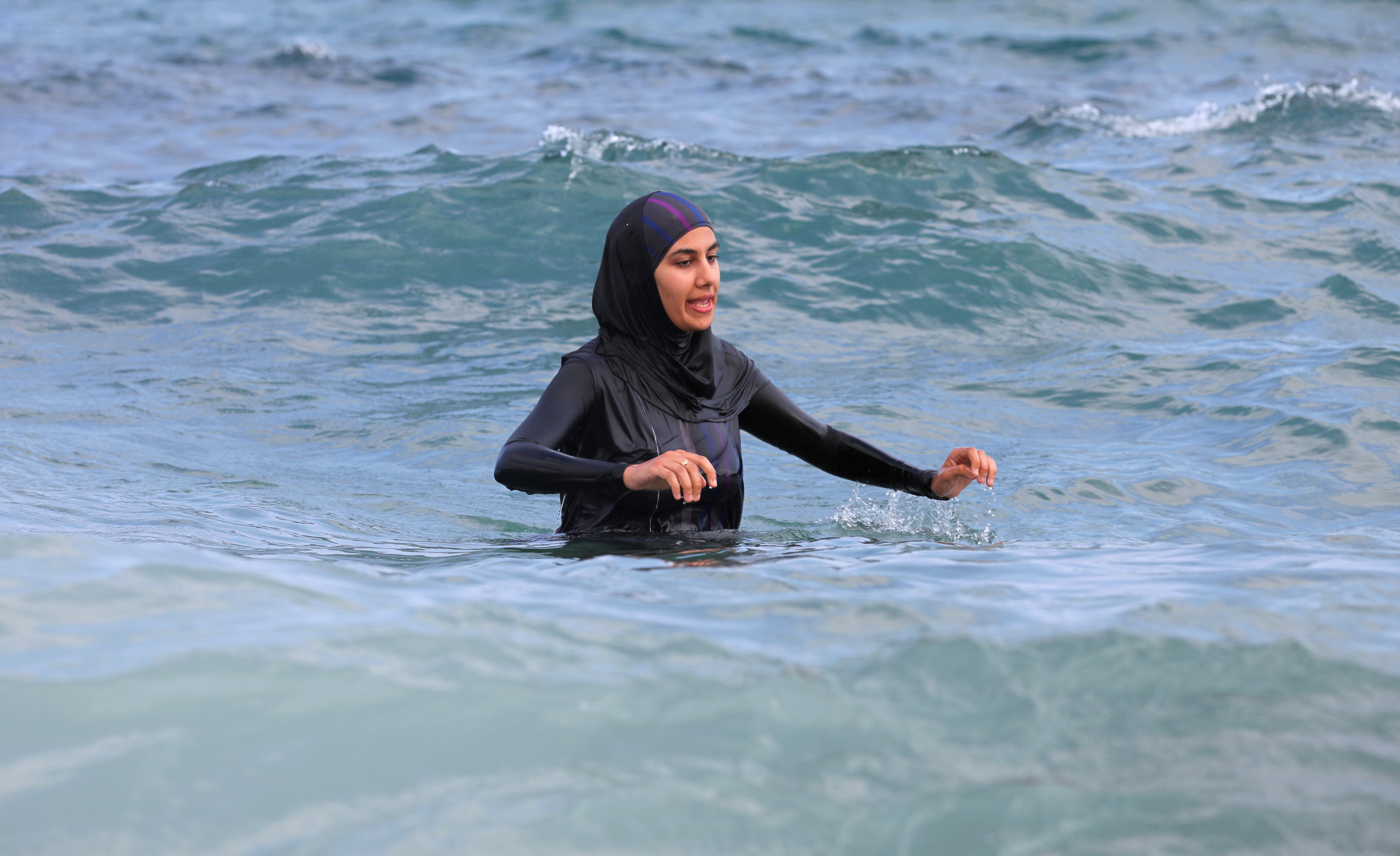 a fully-clothed woman swimming in the Mediterranean Sea in August 2013, photo 1/2