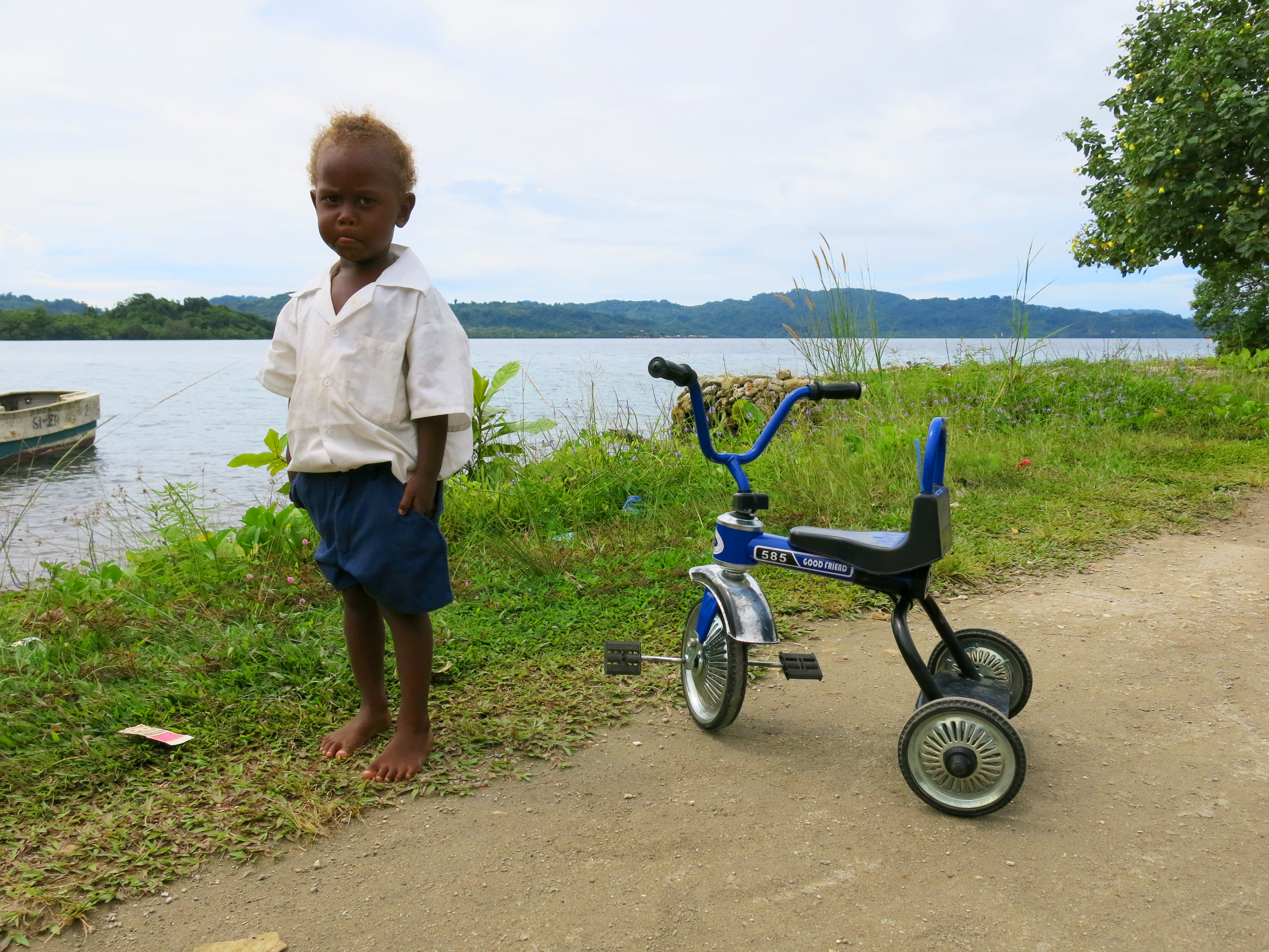 A small boy in a school uniform stands next to his tricycle. (10663272896)