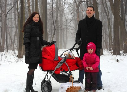a beautiful Catholic family in a foggy and snowy forest
