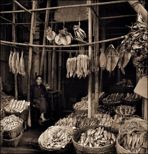 Seated Man Amid Baskets Of Fish & Hanging Dried Fish, Eastern Districts, Hong Kong Island (c1946) Hedda Morrison (RESTORED) (4169611255)