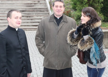 two priests and a beautiful young brunette Catholic woman