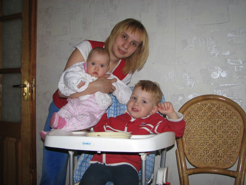 Mother with her baby kids at a table for babies, family.