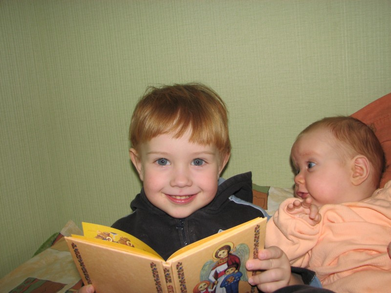 Funny look of a baby sister at her small brother