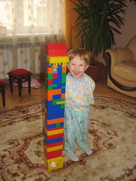 a small boy with one of his first constructed buildings