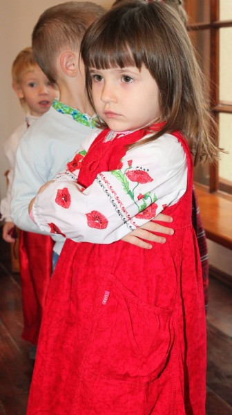 a beautiful amazing cute charming Catholic child girl in a red dress in a Church, photo 1