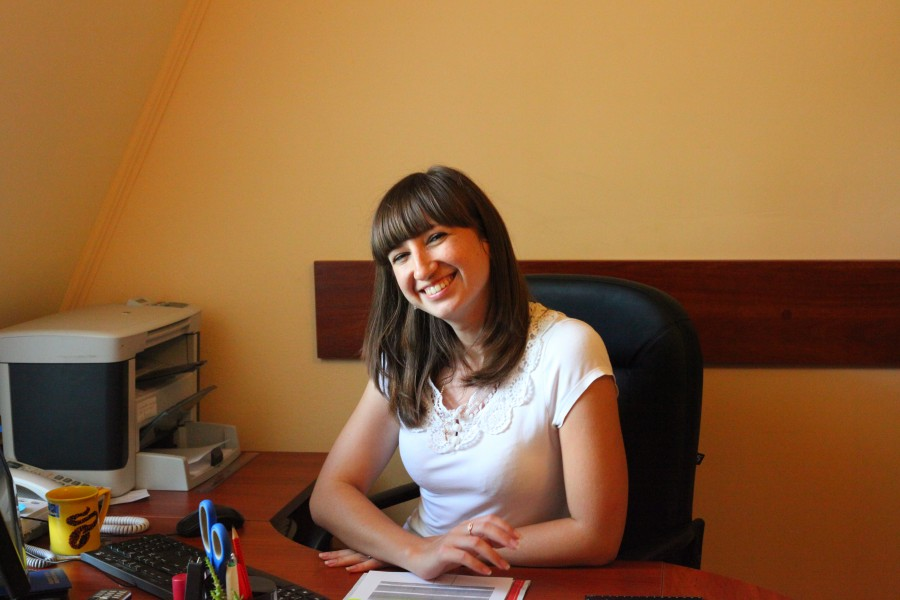 A cute brunet Catholic Christian girl at an office table, photo 2.