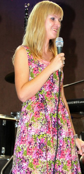 a blond girl in a colorful dress holding a microphone at a protestant gathering in July 2013, image 4/7