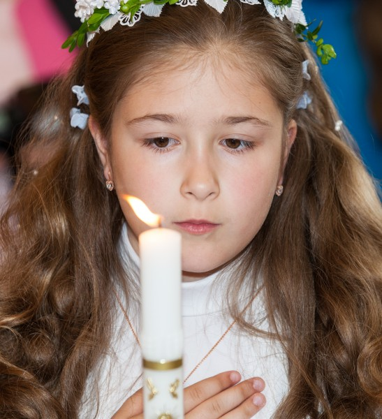 a Catholic child girl with a candle on her first Holy Communion Mass in June 2014, picture 4/4