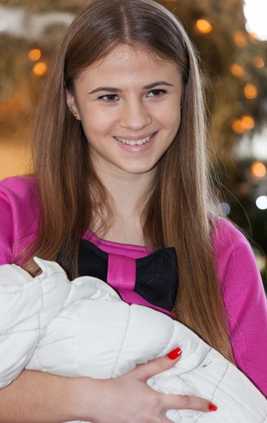 a cute Catholic girl holding her godchild, photographed in December 2014, picture 8