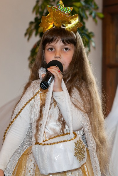 a cute Christian kid girl performing in a Catholic kindergarten in December 2013