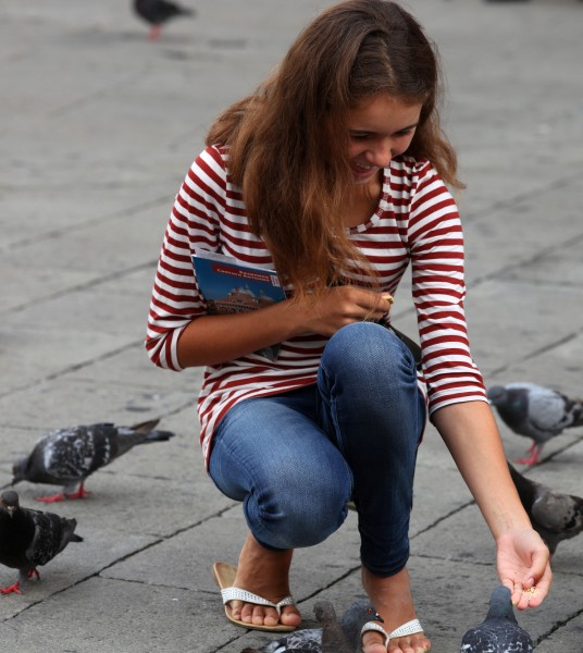 a girl happy to feed pigeons in Padua, Italy, in August 2013