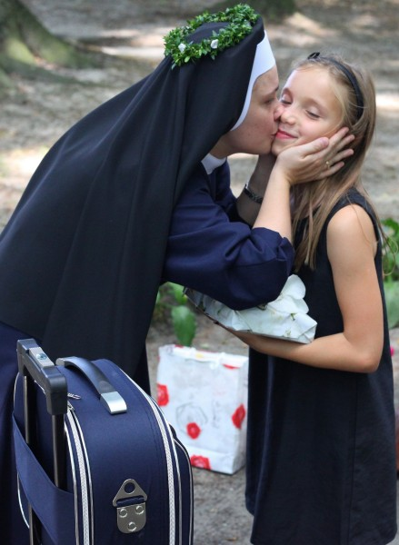 a nun kissing a girl who has just greeted her