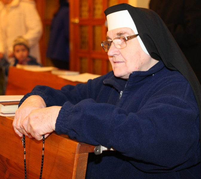 a Catholic nun praying rosary in a Church