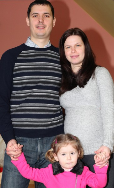 a pregnant beautiful brunette Catholic woman with her husband and daughter, picture 1