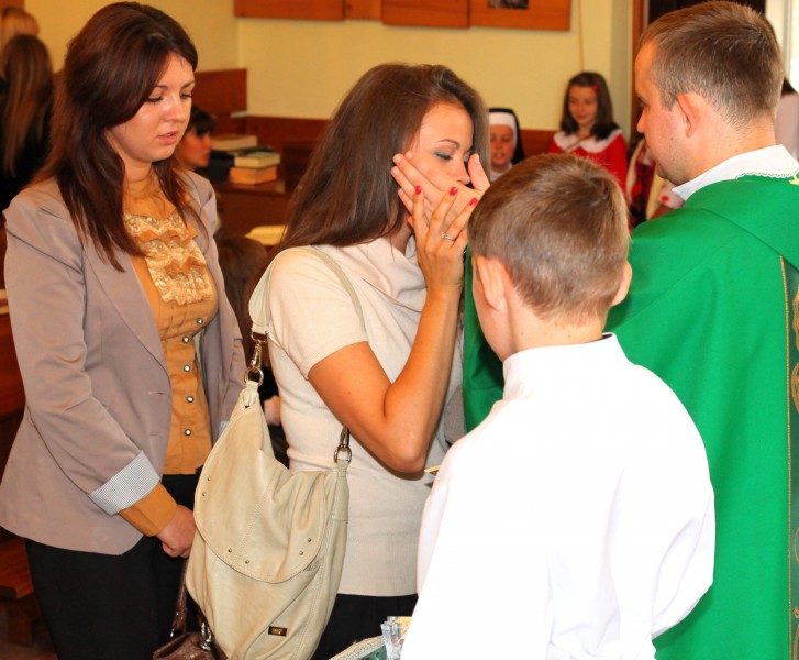 a beautiful charming young Catholic woman kisses the hand of a young padre