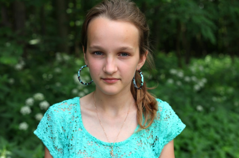 a Catholic girl with huge earrings, photographed in June 2013, portrait 18/27