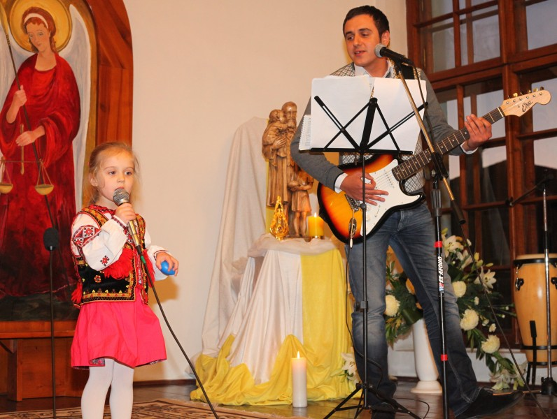 a Catholic father with his daughter performing in a Catholic kindergarten