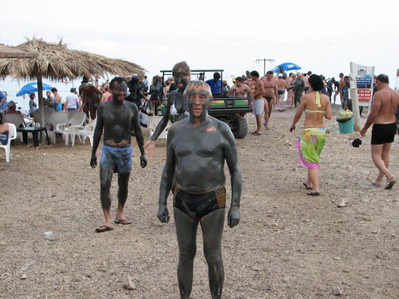 People smeared with dirt on the Dead Sea shore, Israel, 2011