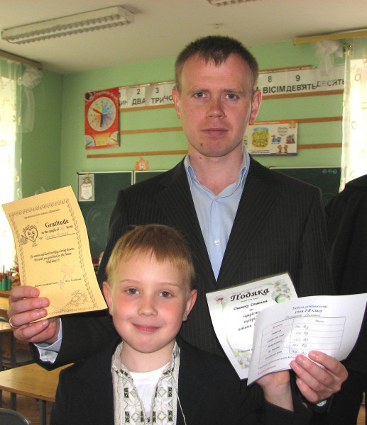 Father and son, with son's school achievement documents.