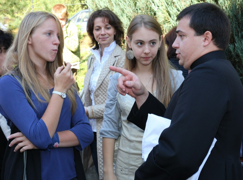 girls and a priest near a Catholic Church after the Holy Mass
