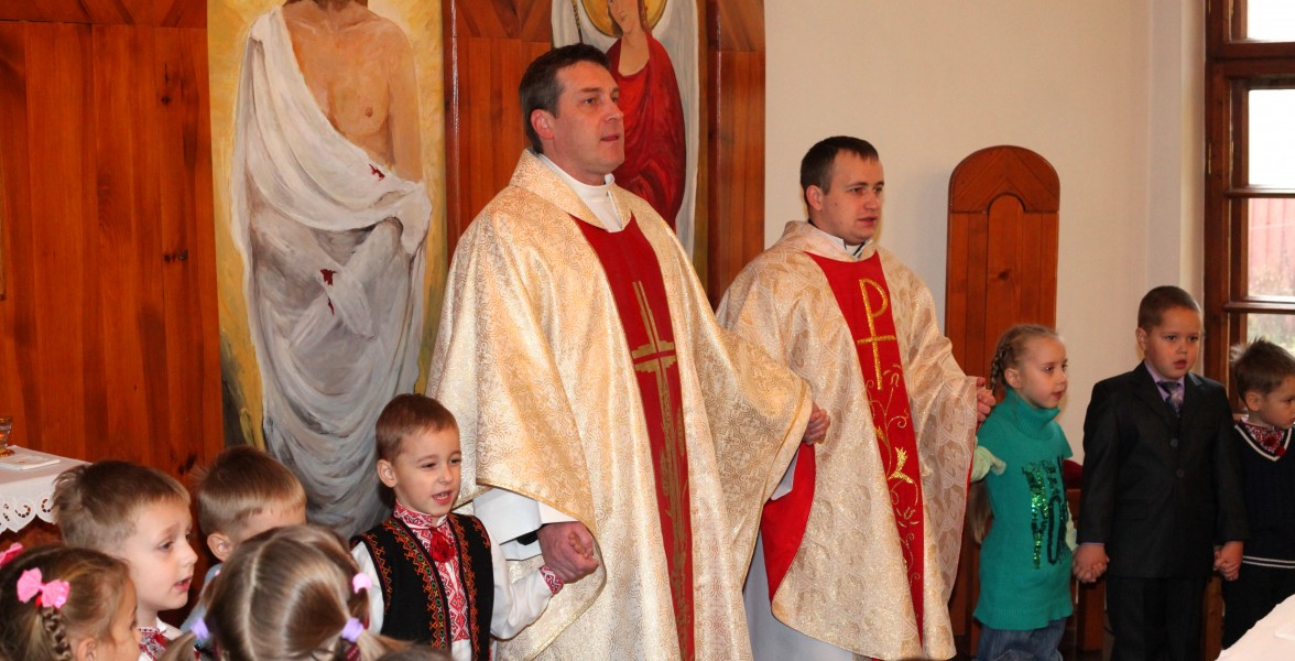kids praying with priests at a Holy Mass in a Catholic Church