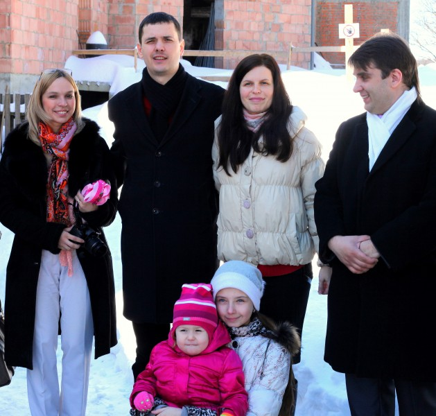 parents and godparents after the baptism of their baby-daughter in a Catholic Church