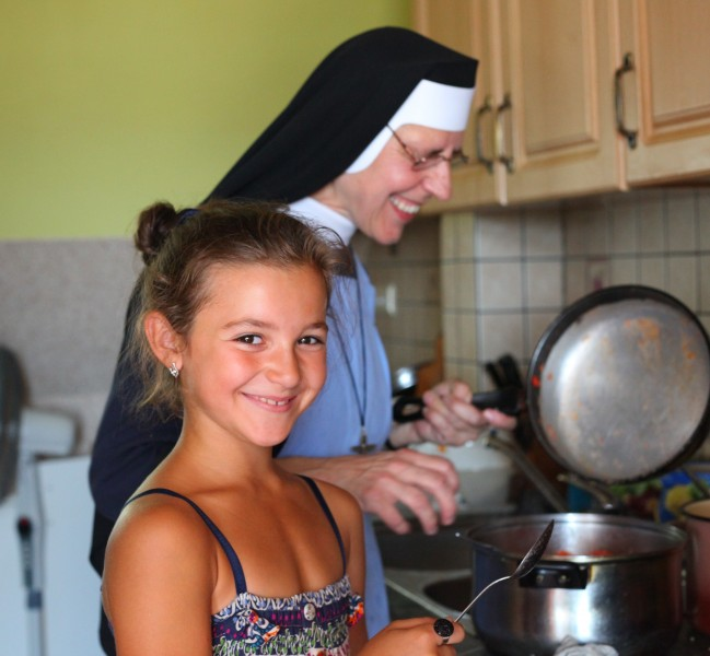 A cute smiling dark-haired Catholic girl, with a nun in background