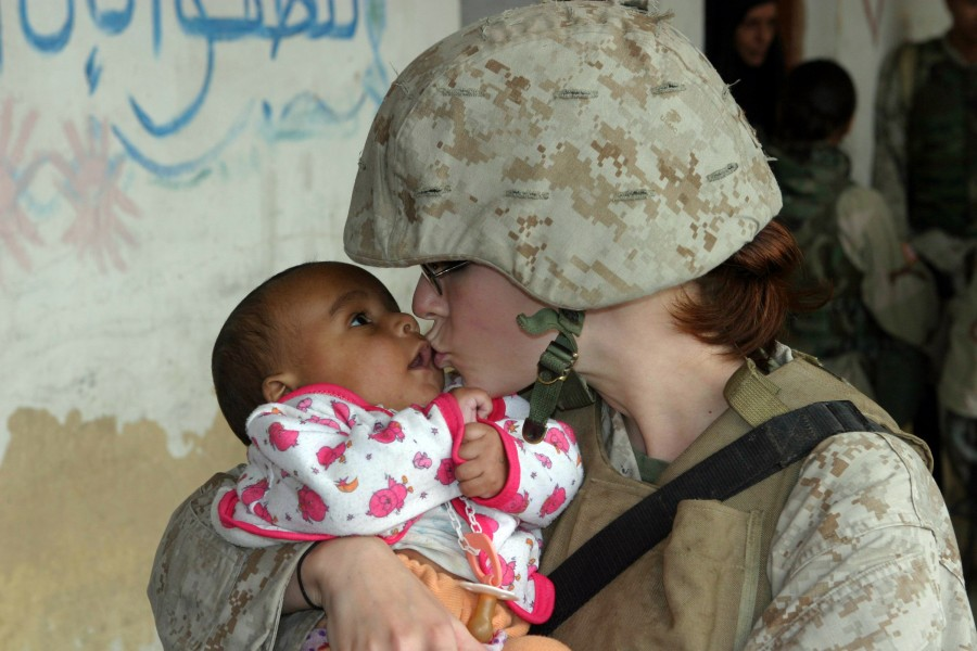US Navy 041112-M-0095Z-181 Lance Cpl. Brandy L. Guerrero gives a kiss to an Iraqi baby waiting to be examined during a Humanitarian Assistance Operation (HAO) in the village of Ash Shafiyah, Iraq